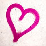 Pink heart on concrete wall. Pink heart shaped on grungy wall background. Metaphor to urban and romantic Valentine, grungy style Royalty Free Stock Image