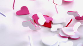 Pink heart confetti dropping on the floor. In slow motion stock footage