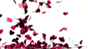 Pink heart confettis falling down. In slow motion stock video footage
