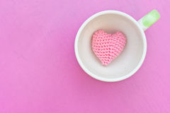Pink heart in cup. Pink heart in the coffee cup on pink table Royalty Free Stock Photography