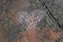 Pink Heart Drawn on a Red Rock Surface. Cute pink heart drawn on a colorful rock surface. Beautiful red and black stone with green lichen on it. Romantic, cute royalty free stock image