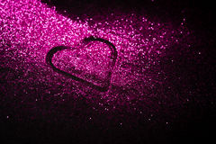 Pink heart in glitter with copy space. Pink glitter shaped as a heart on black background. Copy space Royalty Free Stock Photos