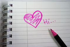 Pink Heart Love Note. Pink heart on spiral notebook sheet with text and a pink marker Stock Image