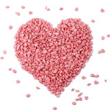 Pink heart - love symbol. A pile of pink stones - bath salt forming a heart - love symbol, isolated on white stock images