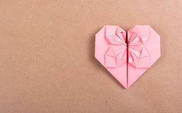 Pink heart made of paper on a brown paper background. Heart of origami Royalty Free Stock Photography