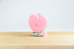 Pink heart Measuring Tape on white background. Pink heart Measuring Tape on wood and white background Royalty Free Stock Photography