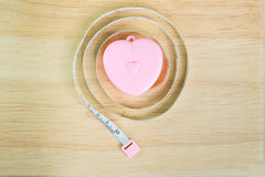 Pink heart Measuring Tape on wood. Background Stock Images