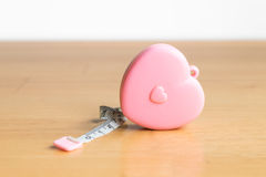 Pink heart Measuring Tape on wood. And white background Royalty Free Stock Photo