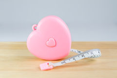 Pink heart Measuring Tape on wood. And white background Stock Images