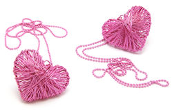 Pink Heart Necklaces. Two metallic pink wired heart pendants on ball chains isolaetd on white background Royalty Free Stock Photo