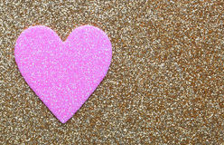 Pink Heart over Gold Glitter background. Valentines Day Card. Macro Stock Photo