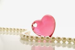 Pink heart and pearls. Pink heart and white pearl necklace over white background Royalty Free Stock Photo