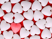 Pink heart between a pile of white hearts. Candy Hearts Royalty Free Stock Images