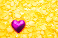 Pink heart. On a pile of yellow rose petals Royalty Free Stock Photos