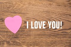 Pink heart post-it with the text `I love you` on a wooden background stock images