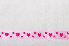 Pink heart ribbon on cloth background Stock Images