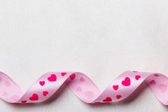 Pink heart ribbon on cloth background Royalty Free Stock Photos