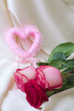 Pink heart and roses. On a silk background Royalty Free Stock Photo