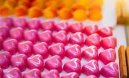 Pink heart shape chocolate. Valentine`s day gift. White chocolate ganache with rose scent on white plate. Chocolate pralines. Luxury chocolate candy. Delicious stock photography