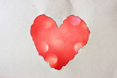 Pink heart shape made from torn paper over glitter boke soft lights. Royalty Free Stock Image