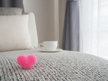 Pink heart shape sign on modern vintage sofa and white coffee cu. P with blurry beautiful white drape window texture background at living room, concept of health Royalty Free Stock Photos