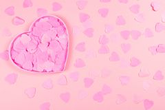 Pink heart-shaped box full of confetti hearts royalty free stock photo