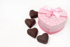 Pink heart shaped box with hearts of chocolate.  Stock Photo