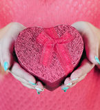 Pink heart-shaped box. In his hands, close-up Royalty Free Stock Photos