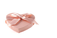 Pink heart-shaped box with purple ribbon knot. On white background Stock Image
