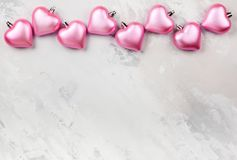 Pink Heart-shaped Christmas ornaments. On the light gray vintage background Royalty Free Stock Image