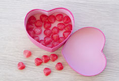 Pink heart-shaped gift box, inside a red heart-shaped candy for Stock Image