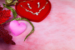 Pink heart-shaped and jewelry in red velvet box. On paper background for a Valentine's day, love concept Royalty Free Stock Photography