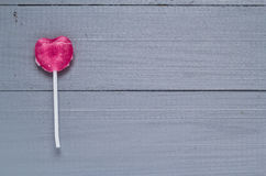 Pink heart shaped lollipop gray boards Royalty Free Stock Images