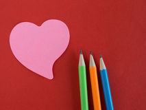 Pink heart-shaped memorandum on red paper with colorful pencils Royalty Free Stock Photography