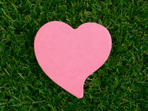 Pink heart-shaped notpad on the artificial grass Royalty Free Stock Image