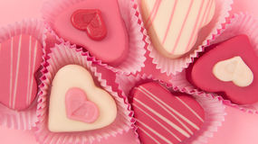 Pink heart shaped petit fours cakes seen from above in a banner size frame. On a pink background Stock Photo