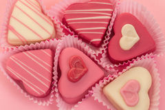 Pink heart shaped petit fours cakes seen from above decorated around pink letters stating Love. Pink heart shaped petit fours cakes seen from above on a pink Royalty Free Stock Photos
