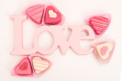 Pink heart shaped petit fours cakes seen from above decorated around pink letters stating Love. On a white background Stock Photo