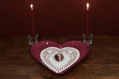 Pink heart shaped plate with dollie and gemstone, two red candles in crystal holders on wooden table. royalty free stock photos