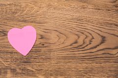 Pink heart post-it on a wooden background. Translation: `I love you` royalty free stock image