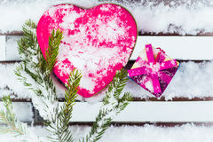 Pink  heart shaped tin box with a gift box. And a fragment of a pine-tree branch on a bench covered with snow Royalty Free Stock Photo