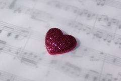 Pink Heart. A sparkling pink heart on top of blurred sheet music royalty free stock images
