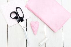 Pink heart stitched with his hands on a white wooden background. Handmade flat lay Royalty Free Stock Images