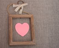 Pink heart in wooden border on canvas. Top view. Valentine card royalty free stock photos