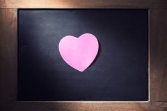 Pink hearted shape post-it note on blackboard. Empty pink hearted shape post-it note on blackboard with concentrated light beam for dramatic feel, vintage retro Stock Photography