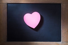 Pink hearted shape post-it note on blackboard. Empty pink hearted shape post-it note on blackboard with concentrated light beam for dramatic feel, vintage retro Royalty Free Stock Photo