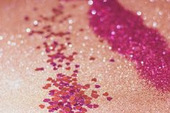 Pink hearts confetti. Photograph of pink hearts confetti on a sparkly gold glitter background royalty free stock images