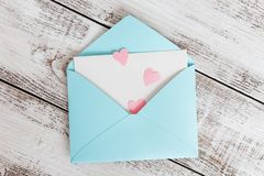 Pink hearts fly out of craft paper envelope on the light wooden background. Valentine day. Love concept stock images