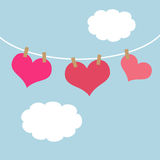 Pink hearts hanging on a clothes line. Three pink hearts hanging on a clothes line surrounded by fluffy white clouds Royalty Free Stock Photos