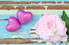 Pink hearts and pink roses on grungy light blue wooden backgroun royalty free stock photos